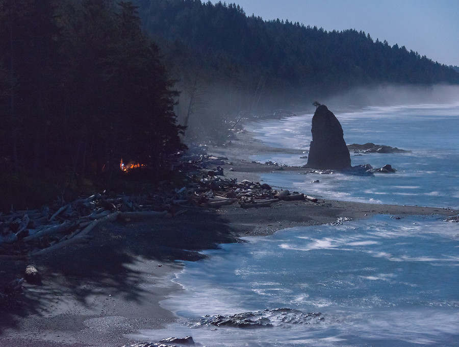 Our camp fire burns as the moon illuminates the Pacific waters of Olympic National Parks Wild Coast.